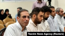 IRAN -- Vahid Mazloumin (L) is seen appearing in court for the first time on charges of manipulating the currency market. He was later sentenced to death, in Tehran, September 8, 2018