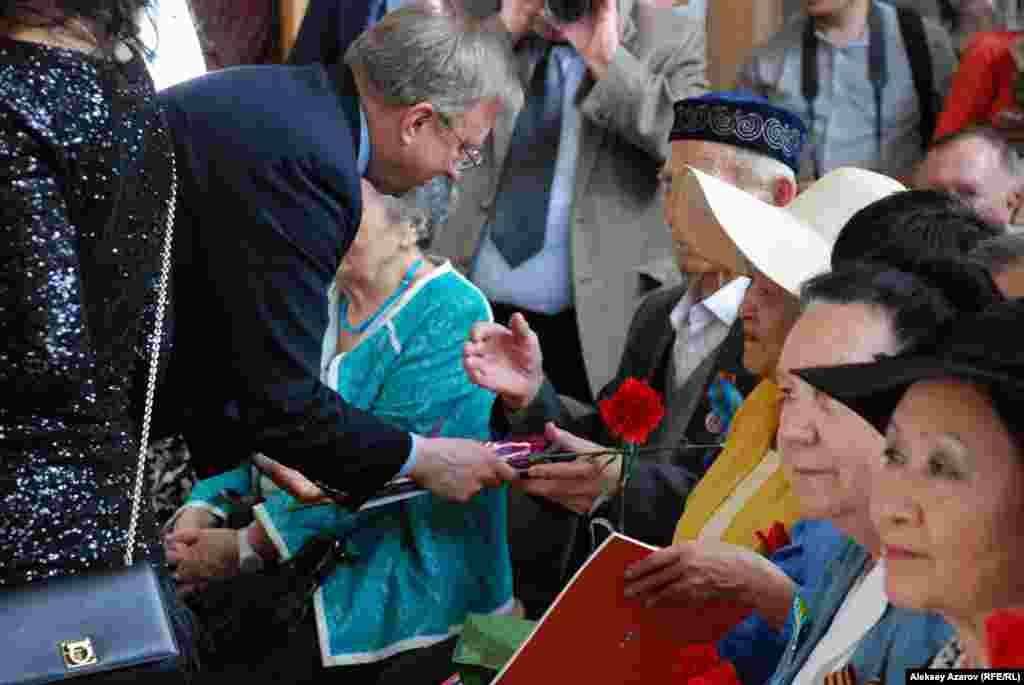 Пососл США в Казахстане Джордж А. Крол поздравляет каждого пришедшего на фотовыставку ветерана фронта и тыла, вручая по красной гвоздике.