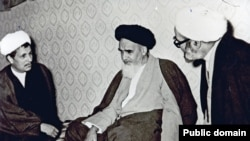 Akbar Hashemi Rafsanjani (left) and Supreme Leader Ruhollah Khomeini (center) in an undated photo