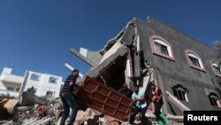 Palestinians carry a door from a destroyed house following what police said was an Israeli air strike in central Gaza on July 9.
