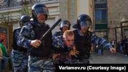 Четверо полицейских ведут 17-летнего Евгения Шпанова в автозак