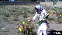 A woman pays her respects at Khavaran cemetery.