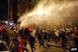 Демонстранты убегают от струй водомета, применяемого полицией. Стамбул, 25 июня 2013 года.