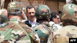 Syrian President Bashar al-Assad greets Syrian army soldiers in Daraya on August 1.