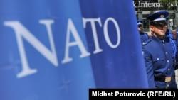 Vojnik Oružanih snaga BiH stoji ispred banera na kojem je zastava NATO-a, Sarajevo, fotoarhiv