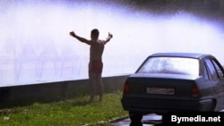 Belarus -- The young man refresh himself and his car in a cloud of spray from the fountain