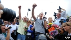 """Российский оппозиционный политик Алексей Навальный приветствует сторонников и журналистов после возвращения из Кирова, где он был сначала осужден к пяти годам тюрьмы по """"делу Кировлеса"""", затем выпущен под подписку о невыезде. Москва, 20 июля 2013 года."""