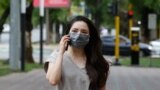 Kazakhstan. A girl in a protective mask is walking along the street of Almaty. June 22, 2020