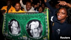 Люди собрались около дома Нельсона Манделы в ЮАР после известий о его кончине. Хоутон, 5 декабря 2013 года.