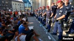 Біженці сидять поруч з поліцією біля входу на головний залізничний вокзал Будапешта. 1 вересня 2015 року