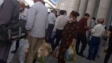 Turkmenistan. Man and woman with bags. Crowd of people. Turkmenbashi. August 2021