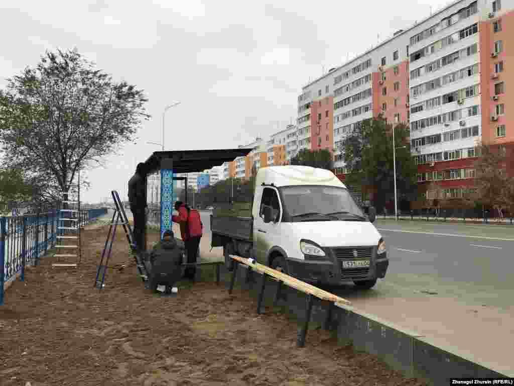 Рабочие устанавливают новую остановку по улице Маншук Маметовой.