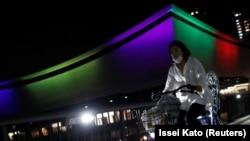 Женщина проезжает мимо Ариаке Арены, освещенной цветами олимпийских символов в день, знаменующий годичный обратный отсчет до Олимпийских и Паралимпийских игр в Токио 2020, которые были перенесены на 2021 год из-за вспышки коронавирусной болезни (COVID-19), 23 июля 2020 г.