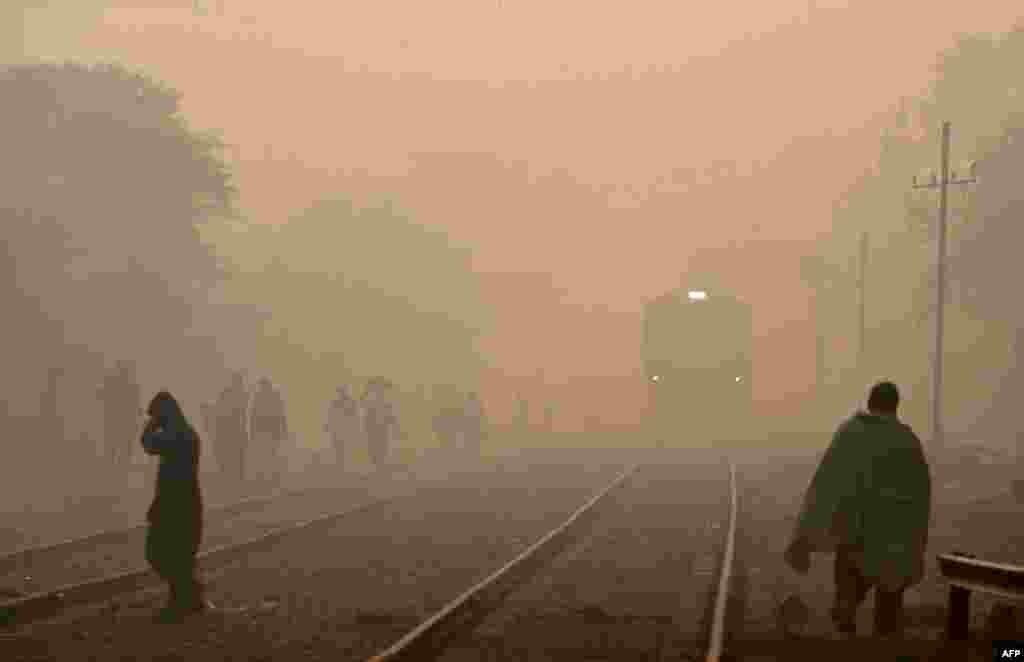 Людзі ідуць уздоўж чыгункі ў туманны дзень у Лагоры, Пакістан. (AFP/Arif Ali)