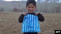 Murtaza Ahmadi, 5, poses with his plastic-bag jersey in January 2016.
