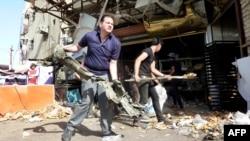 عراقيون ينظفون آثار تفجير في مدينة الصدر ببغداد