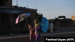 Afghan schoolgirls walk along a street on the outskirts of Mazar-e Sharif (file photo)