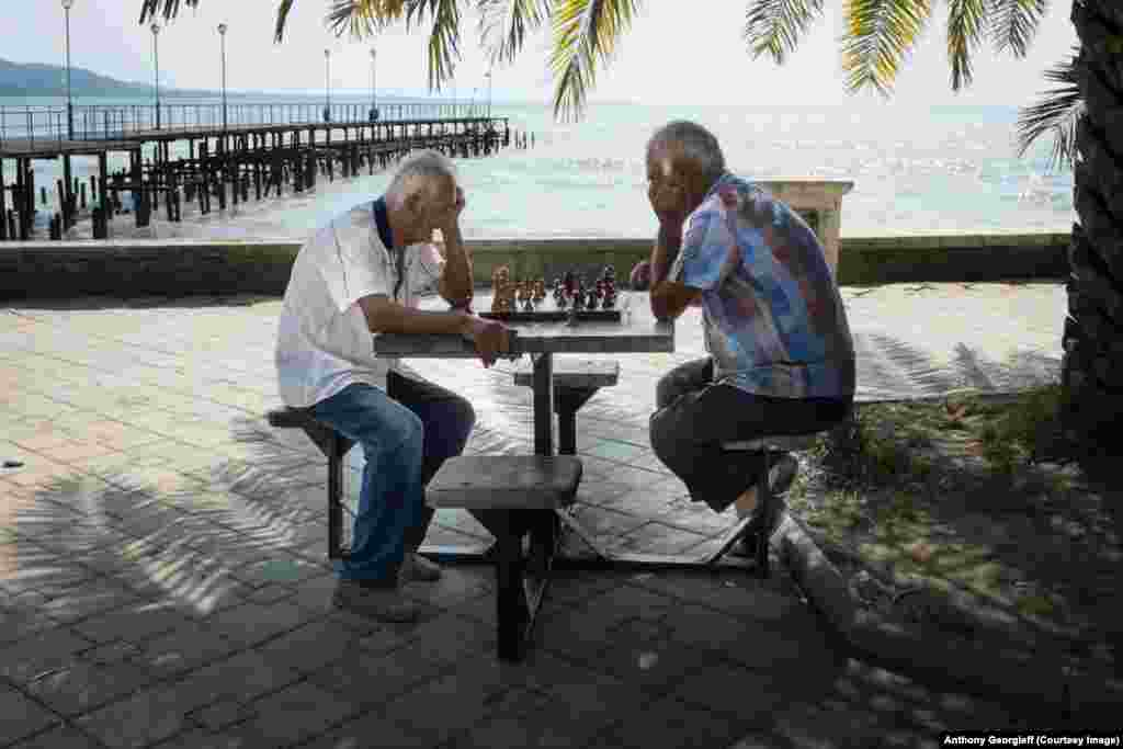 Men play chess in front of one of Sukhumi's abandoned piers.