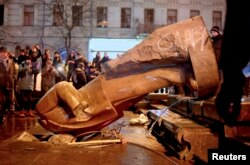 People surround the Lenin statue after it was toppled by protesters in Kyiv on December 8, 2013.
