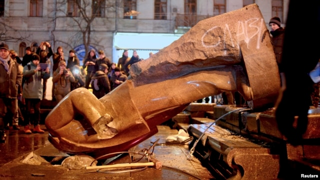 People surround a statue of Soviet state founder Vladimir Lenin that was toppled by protesters during a rally organized by supporters of EU integration in Kyiv on December 8, possibly setting off the rash of Lenin-idolatry abuse.