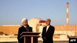 Президент Ірану Хасан Роугані (л) і голова Організації з атомної енергії Ірану Алі Акбар Салехі на тлі АЕС у Бушері, 2015 рік