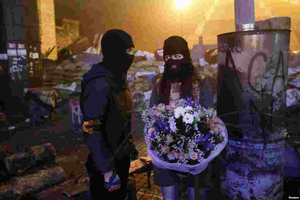 An activist from the Right Sector antigovernment protest group presents a bouquet of flowers to his girlfriend in front of fellow activists near the site of previous clashes with riot police in Kyiv on February 13. (Reuters)