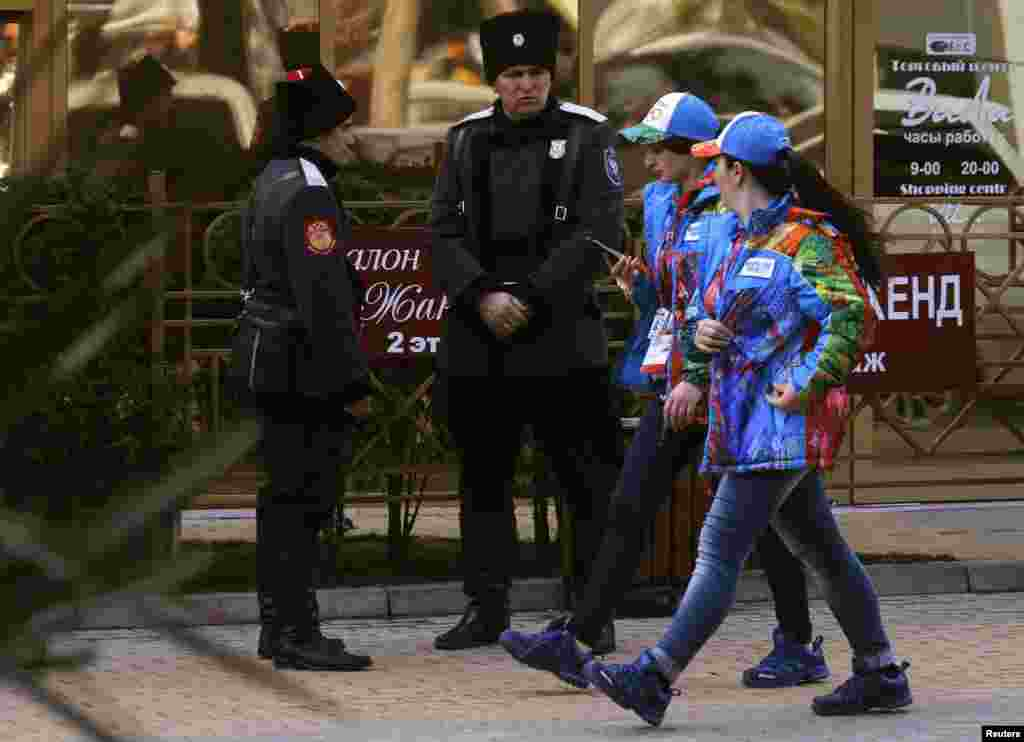 Olympic volunteers walk in front of Russian Cossacks who patrol the Adler district of Sochi. (Reuters/Aleksandr Demianchuk)
