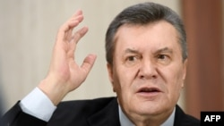 Former Ukrainian President Viktor Yanukovych gestures as he answers journalists questions during a press conference in Moscow in February.
