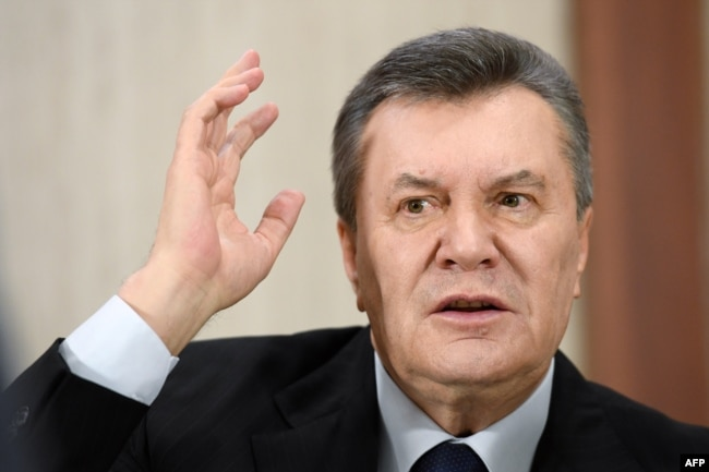 Former Ukrainian President Viktor Yanukovych gestures as he answers journalists' questions during a press conference in Moscow on February 21.