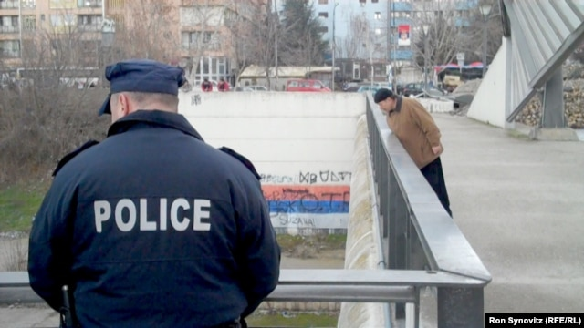 Members of the Kosovo Police Force stand guard on the central bridge in Mitrovica.