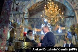 Russian President Vladimir Putin prays during a visit to the monastic community of Mount Athos in Karyes in May 2016.