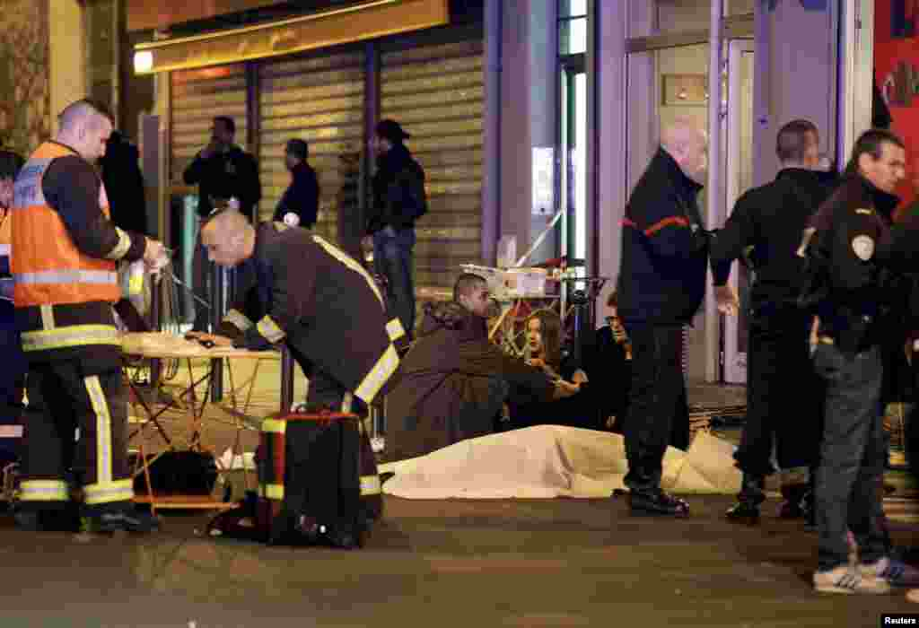 A French rescue worker checks his laptop computer as three people consol each other over the body of a shooting victim.