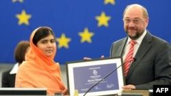 Малала Юсуфзай (сол жақта) Еуропа парламентінің президенті Мартин Шульцтен Сахаров сыйлығын алып тұр. Страсбург, 20 қараша 2013 жыл.