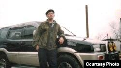 Осужденный Виктор Боровик позирует на фоне автомобиля. Его родственники говорят, что фото сделано на территории колонии 159/22.
