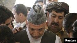 Presidenti i Afganistanit Hamid Karzai në varrimin e vëllaut të tij...