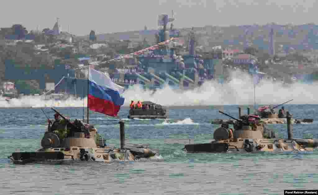 Amphibious vehicles drive in formation past the Russian missile cruiser Moskva during a rehearsal for the Navy Day parade in the Black Sea port of Sevastopol, Crimea. (Reuters/Pavel Rebrov)
