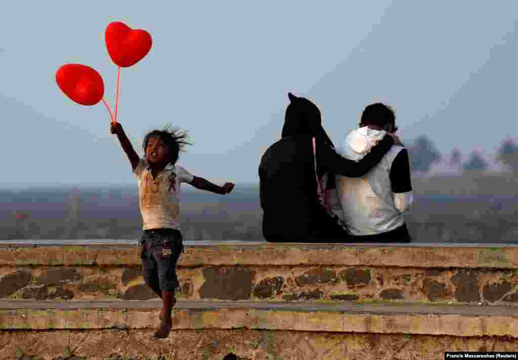 A child jumps from a promenade after attempting to sell heart-shaped balloons to a couple on Valentine's Day in Mumbai. (Reuters/Francis Mascarenhas)