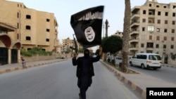 """Боевик группировки """"Исламское государство"""" с черным знаменем. Ракка, 29 июня 2014 года."""