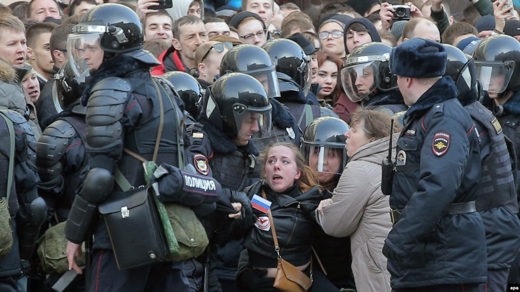 Russian riot police detain a demonstrator during an opposition rally in central Moscow on March 26.
