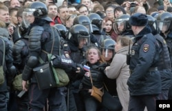 Russian riot policemen detain a demonstrator during an opposition rally organized by Navalny in central Moscow on March 26.