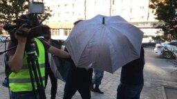 В Нур-Султане неизвестные чинят помехи сотрудникам Азаттыка с помощью зонтов, 6 июля 2019 года.
