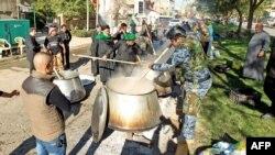 قوات أمن عراقية يشاركون في إعداد طعام لجموع من الزوار