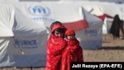 An Afghan internally displaced person holds a child and walks near temporary shelters built by the United Nations High Commissioner for Refugees in Herat in December 2018.