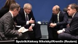 Борис Джонсон и Владимир Путин (в центре) в кулуарах берлинского саммита, 19 января 2020
