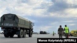 Военная полиция и военные автомобили, машины скорой помощи на перекрытой трассе, ведущей в войсковую часть, где произошли взрывы. Жамбылская область, 27 августа 2021 года