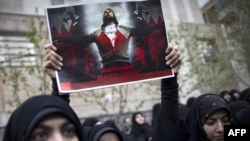 An Iranian student holds up a sign with a picture of a Bahraini protester in front of the Saudi Arabian Embassy in Tehran. Iran has been vocal in its criticism of Saudi actions against Shi'ite protesters in the Persian Gulf state.