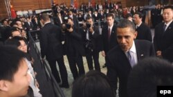 АКШ президенти Барак Обама суроолорго жооп бергенден кийин кытайлык студенттер менен кол алышууда. Шанхай. 16-ноябрь, 2009-жыл.
