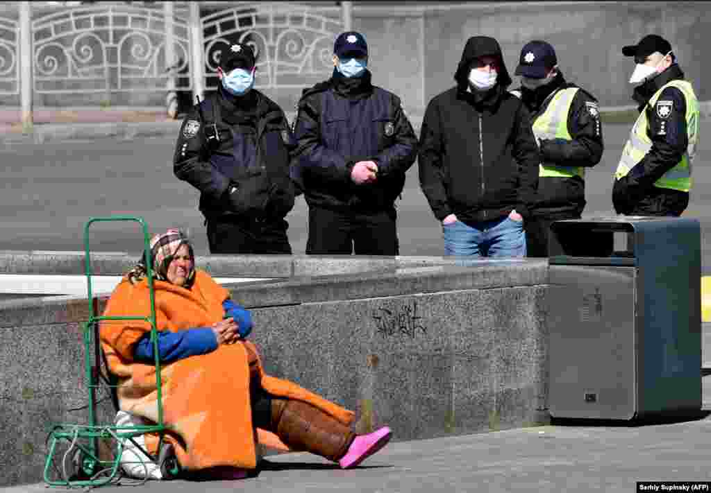 An elderly homeless woman begs in Kyiv, Ukraine, as police wearing face masks patrol the streets amid a coronavirus outbreak. (AFP/Sergei Supinsky)