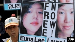 An activist holds up pictures of journalists Laura Ling and Euna Lee, who were detained in North Korea, at a rally in Seoul.