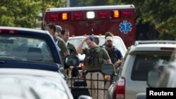 Heavily armed policemen walk from the Washington Navy Yard after the shooting on September 16.